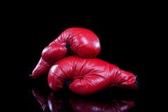 Paires de gants de boxe rouges sur le noir Images stock