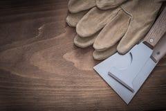 Paires de gants protecteurs en cuir et de grattoirs brillants de peinture Images libres de droits