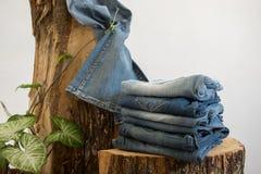 Paires de jeans sur un tronc en bois, fond blanc avec l'espace de copie photos stock
