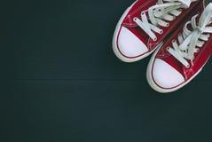 Paires de la jeunesse rouge d'espadrilles sur un fond en bois noir, s vide Photos libres de droits