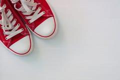 Paires de la jeunesse rouge d'espadrilles sur une surface en bois blanche Photos stock