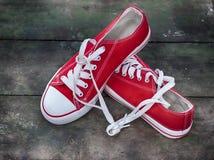 Paires de la jeunesse rouge d'espadrilles sur une vieille surface en bois Photo stock