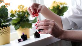 Paires de mains femelles ouvrant la bouteille de vernis ? ongles image stock