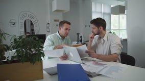 Paires de négociant regardant sur des graphiques et des diagrammes discutant des résultats des ventes banque de vidéos