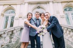 Paires de nouveaux mariés avec le garçon d'honneur heureux et la demoiselle d'honneur posant aux escaliers du bâtiment classique Photos libres de droits