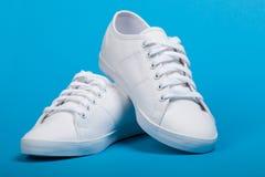 Paires de nouvelles espadrilles blanches sur le fond bleu Photo libre de droits