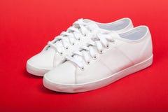 Paires de nouvelles espadrilles blanches sur le fond rouge Photo libre de droits
