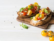 Paires de pains grillés grillés avec le fromage fondu et tranches de tomates fraîches de diverses couleurs avec l'arugula frais e photos stock