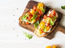 Paires de pains grillés grillés avec le fromage fondu et tranches de tomates fraîches de diverses couleurs avec l'arugula frais e photographie stock libre de droits