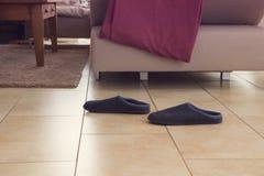 Paires de pantoufles à côté d'un divan photographie stock libre de droits