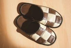 Paires de pantoufles sur le fond en bois de plancher Photographie stock libre de droits