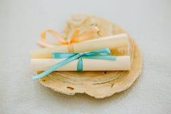 Paires de parchemins de papier de petit pain attachés avec le ruban sur un coquillage, messages d'amour Photo stock