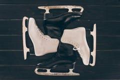 Paires de patins blancs et noirs sur la surface en bois photo stock