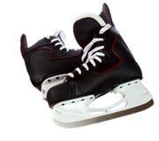Paires de patins noirs d'hockey d'isolement sur le fond blanc Images libres de droits