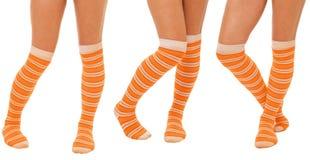 Paires de pattes de femmes dans les chaussettes oranges Photos stock