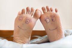 Paires de pieds femelles avec les visages de sourire là-dessus Image stock