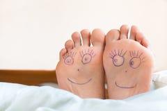 Paires de pieds femelles avec les visages de sourire là-dessus Image libre de droits