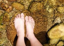 Paires de pieds femelles se tenant dans un courant Photo stock