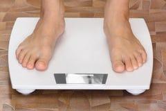 Paires de pieds femelles se tenant sur l'échelle Photos stock