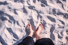 Paires de pieds sur le sable de plage Photos stock