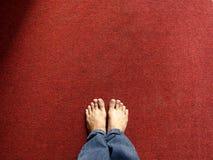 Paires de pieds sur un tapis rouge Photos libres de droits
