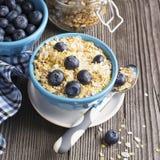 Paires de pleine céréale de petit déjeuner de cuvettes en céramique bleues avec les myrtilles et le lait frais Image stock