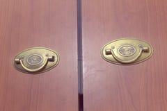 Paires de poignées en laiton de traction de pliage sur les portes en bois de la garde-robe photo stock