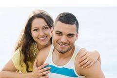 Paires de sourire ayant la date romantique sur la plage sablonneuse Image libre de droits