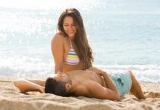 Paires de sourire s'étendant sur la plage de sable Photographie stock