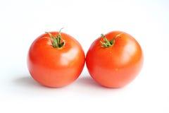 paires de tomates rouges avec les queues vertes sur une serre chaude faite maison de fond blanc Photos libres de droits