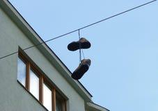 Paires de vieilles bottes brunes accrochant sur le fil Photos stock