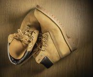Paires de vieilles bottes fonctionnantes jaunes d'isolement sur le fond en bois Photo stock