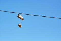 Paires de vieilles chaussures accrochant sur la ligne électrique Photographie stock