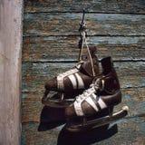 Paires de vintage de patins de glace des hommes accrochant sur un mur Photos stock