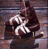 Paires de vintage de patins de glace des hommes accrochant sur un mur en bois Photos stock