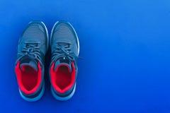 Paires de vue supérieure de chaussures courantes bleues et rouges de sport d'isolement sur le fond bleu-foncé avec l'espace de co photographie stock libre de droits