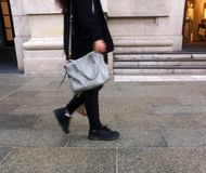 Paires de woman& x27 ; jambes de s marchant sur un trottoir Image stock