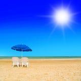 Paires des canapés du soleil et d'un parapluie de plage sur une plage abandonnée Image libre de droits