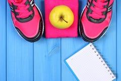 Paires des chaussures de sport et de la pomme fraîche sur les conseils bleus, l'espace de copie pour le texte sur la feuille de p Photo stock