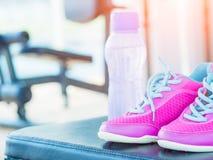 Paires des chaussures et de la bouteille d'eau roses de sport avec l'équipement de forme physique Image libre de droits