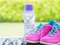 Paires des chaussures et de la bouteille d'eau roses de sport avec le bokeh vert Photos libres de droits