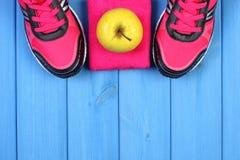 Paires des chaussures roses de sport et de la pomme fraîche sur les conseils bleus, l'espace de copie pour le texte Photo libre de droits