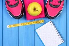 Paires des chaussures roses de sport et de la pomme fraîche sur les conseils bleus, l'espace de copie pour le texte sur la feuill Images stock
