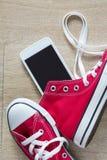 Paires des espadrilles rouges et d'un smartphone Photos libres de droits