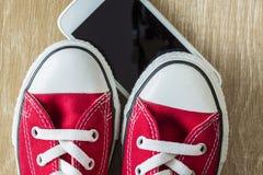 Paires des espadrilles rouges et d'un smartphone Photo stock