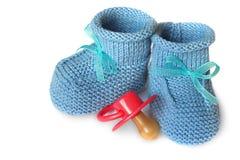 Paires des petits chaussons des enfants bleus de knit et du simulacre du bébé sur un fond blanc Photographie stock