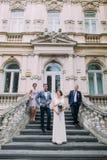 Paires gaies de nouveaux mariés avec le garçon d'honneur heureux et la demoiselle d'honneur posant aux escaliers du bâtiment clas Image stock