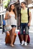 Paires heureuses avec le bagage marchant dans la ville Image stock