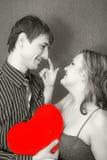 Paires heureuses avec un oreiller de forme de coeur Photographie stock libre de droits