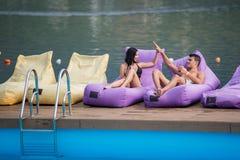 Paires heureuses détendant avec le cocktail et donnant la haute cinq entre eux sur les canapés amortis par la piscine Images stock